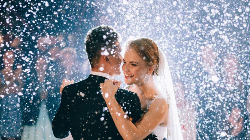 A bride and groom enjoy first dance with a snow machine.