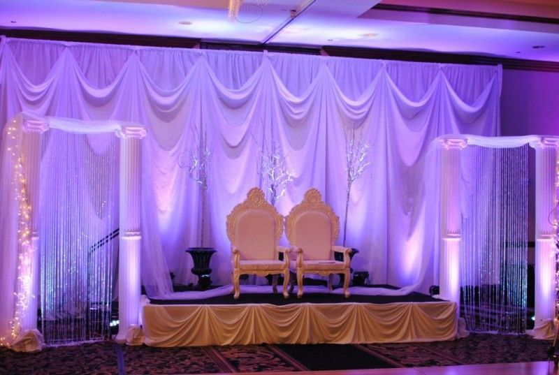 Two chairs on small stage with lavender wedding drapery backdrop behind.