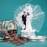 Money jar tipped over with bride and groom cake topper to demonstrate wedding planning