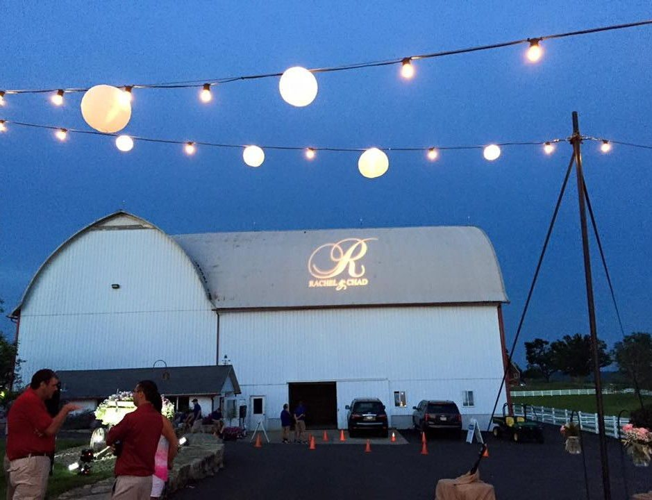 White barn with custom monogram on roof and bistro lighting outside