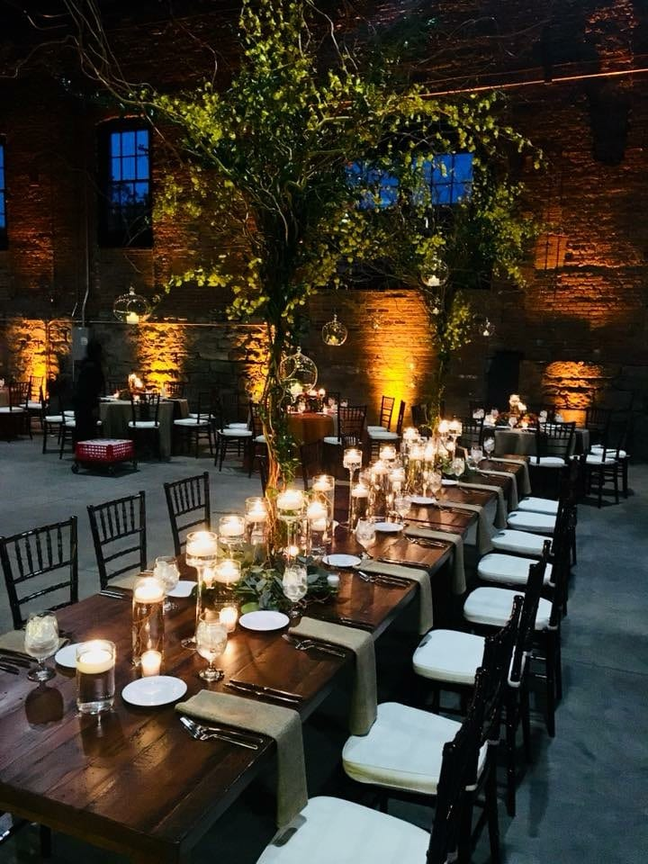 Guest tables at Tenk West Bank wedding venue highlighted with up-lighting.