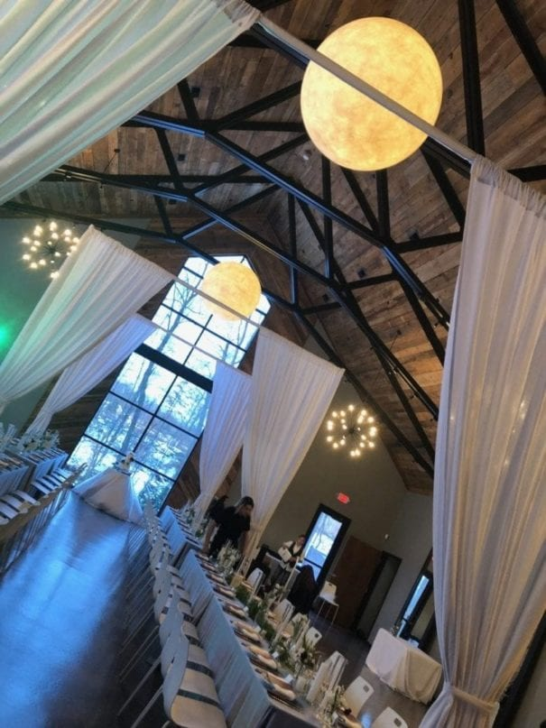 Angled photo of custom wedding drapery at wedding venue, Sapphire Creek Winery. The drapery is a light gray flowy material that still lets light shine through. At the far end of the set reception tables a floor to ceiling window lets in warm light as well as the natural beauty from outside. Spherical chandeliers hang above.