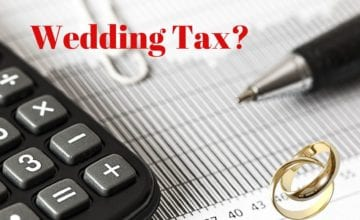 "Calculator, pen and paper with text reading ""wedding tax""."