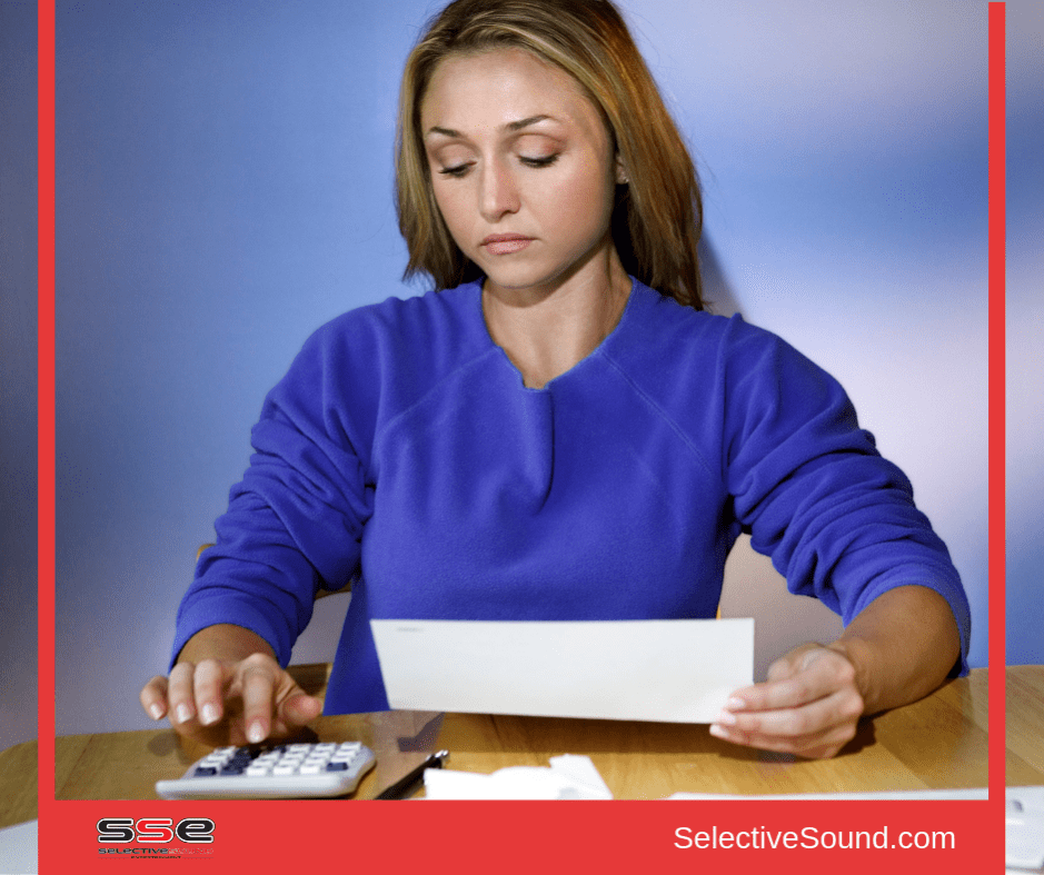 Woman at desk with calculator, determining wedding budget.