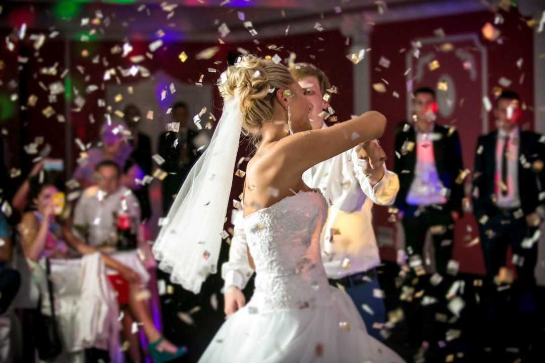 Beautiful Bride Dancing through a blast from confetti cannons