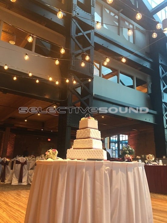 Wedding cake at Windows on the river with bistro lighting strung above.