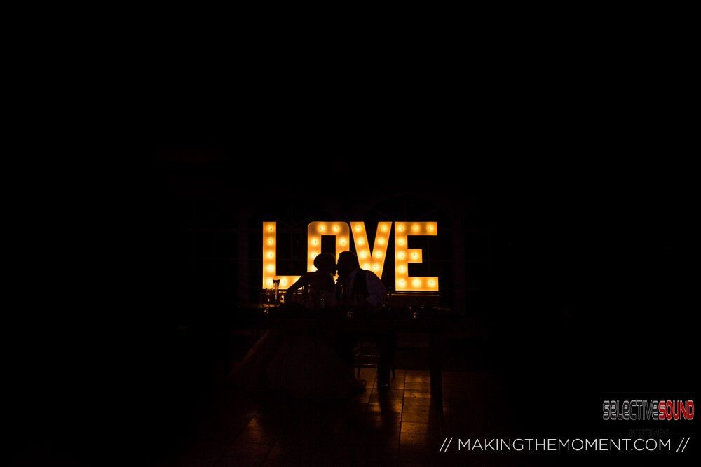 Wedding LOVE letters glowing behind silhouette of bride and groom with black background.