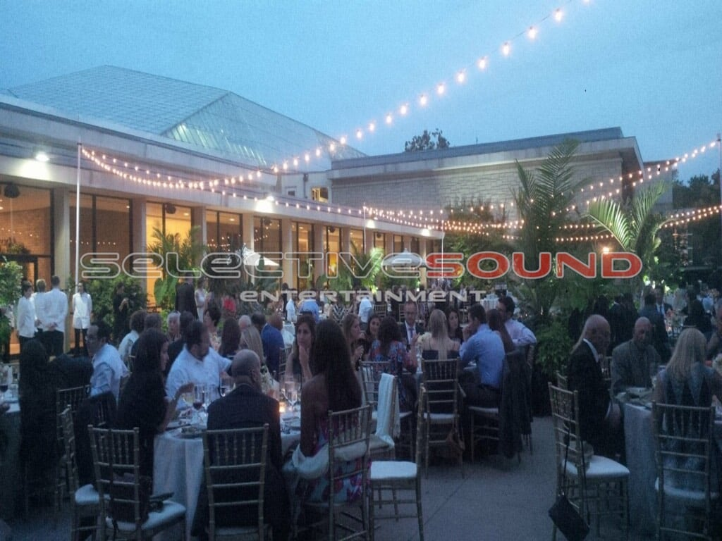 Wedding guests dining el fresco at Cleveland Botanical Gardens with Bistro lighting glowing above