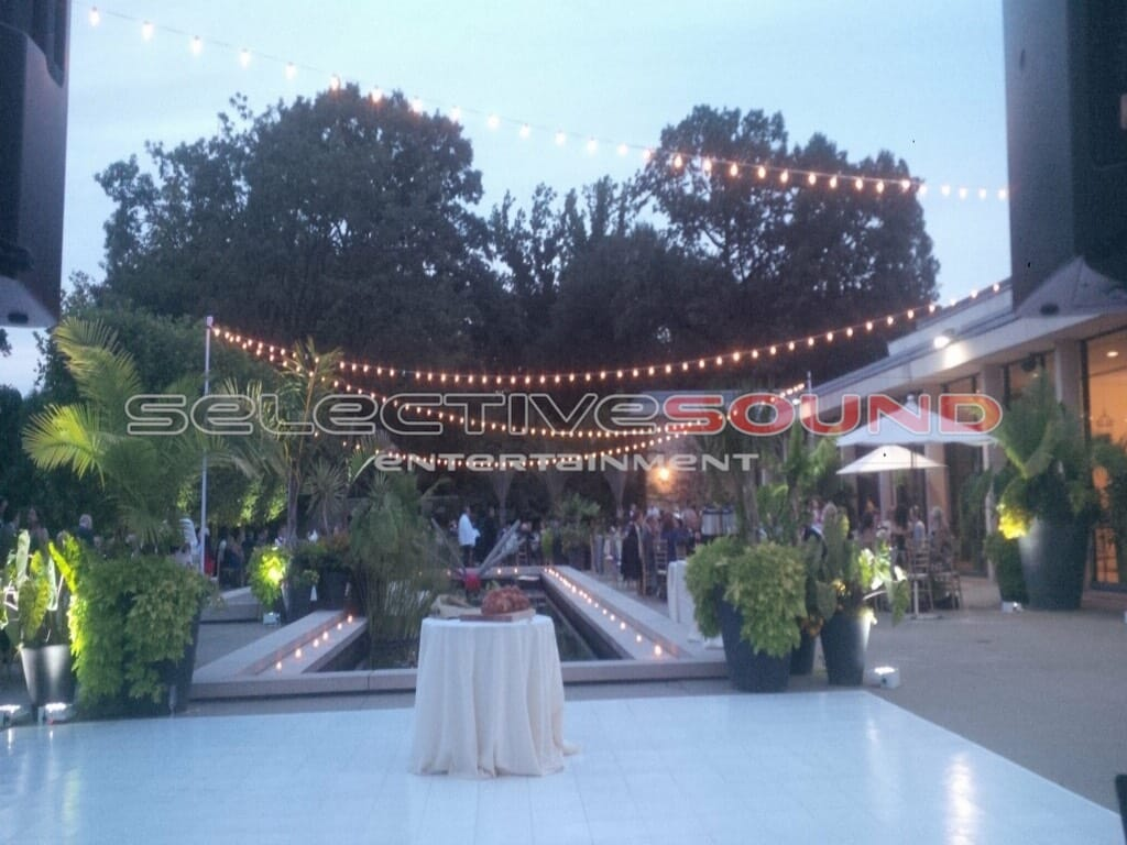 Guests gather under bistro lighting outside at dusk for wedding reception at Cleveland botanical gardens