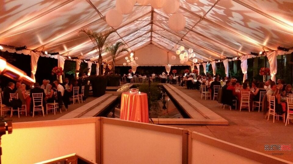 Guests sitting under beautiful wedding tent lighting by Selective Sound Entertainment