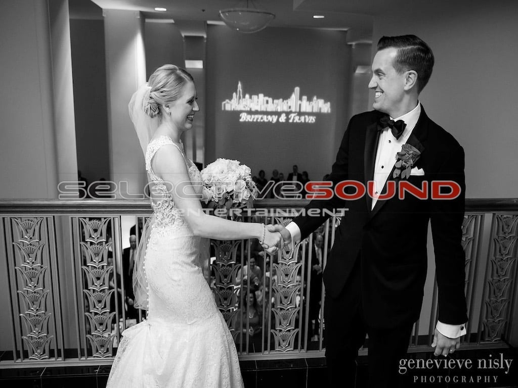 Custom designed monogram sits in the background of Bride and groom posing for picture at the Cleveland Silver Grille.
