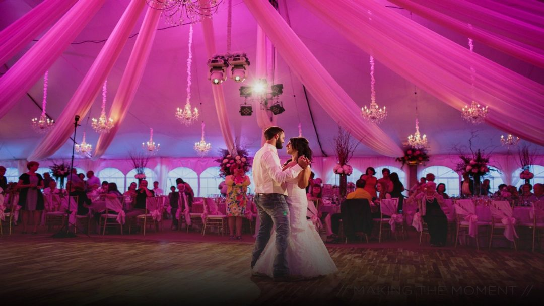 Bride and groom dancing inside giant tent with unique lighting and chandeliers