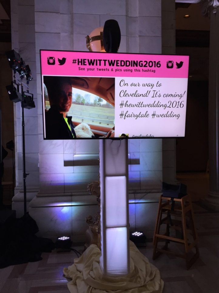 wedding social cast on screen at reception