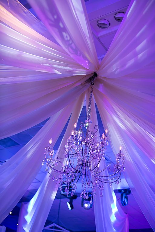 Chandeliers hung in the center of hanging drapery