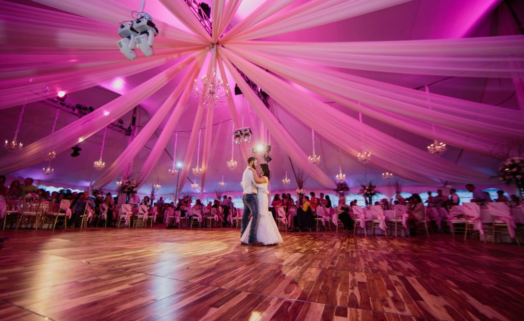 bride and groom dancing inside giant tent decorated with pink lighting, chandeliers and feature spotlighting