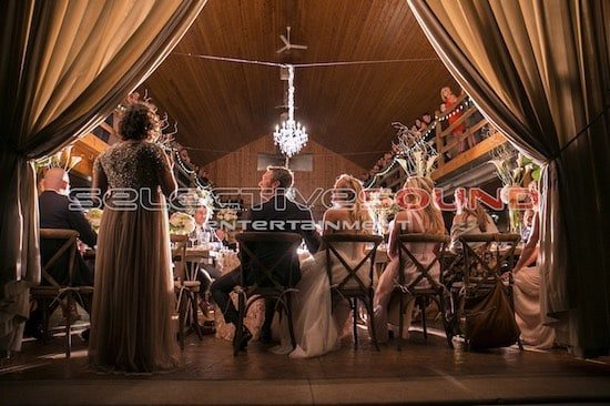 Maid of honor giving toast in barn