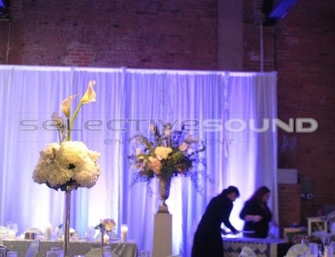 Beautiful crushed white backdrop in front of oxidized brick wall with pin spotting to light up centerpiece