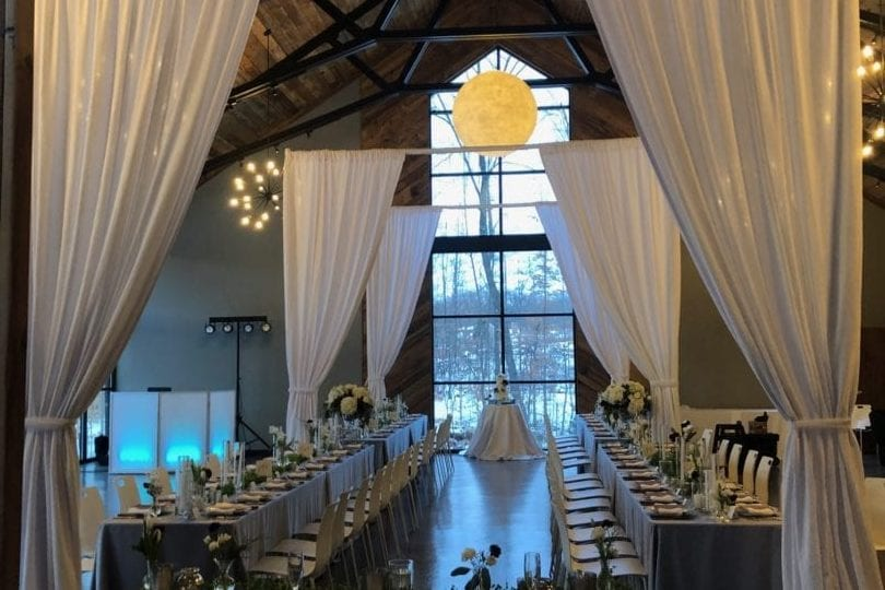This picture shows the view of the custom wedding drapery from just behind the head table at the reception venue. The drapery is a light gray flowy material that still lets light shine through, making the room still feel large rather than cutting it off with dark opaque curtains. At the far end of the gray and white dressed reception tables a floor to ceiling window lets in warm light as well as the natural beauty from outside. Spherical chandeliers hang down from the wooden beam covered ceiling.