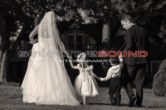 Bride and groom stroll outdoors with the flower girl and Ring bearer