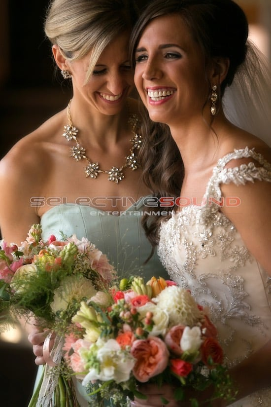 Bride And Sister laugh together at wedding reception