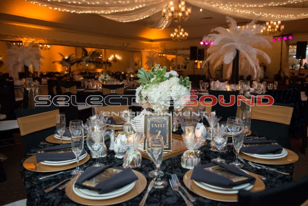 Room shot with amber uplighting in background at Great Gatsby themed wedding
